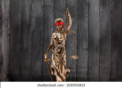 Justitia with blindfold in front of wood background as a justice concept