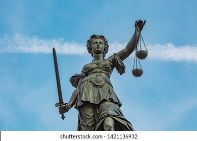Justitia Figurine holds up the Scales of Justice