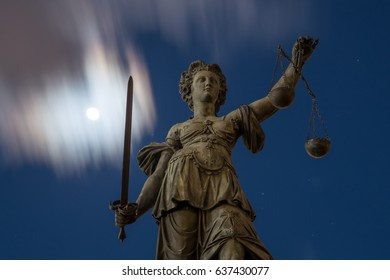 Justitia sculpture at old town of Frankfurt city, Germany, at moonlit night.