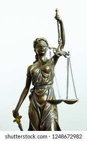 Justitia statue with blindfold, sword and balance, white background