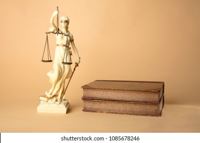 Justizia Figure with old Books on beige Background