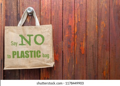 Jute bag with No plastic logo hanging on old wooden wall, ecological object concept