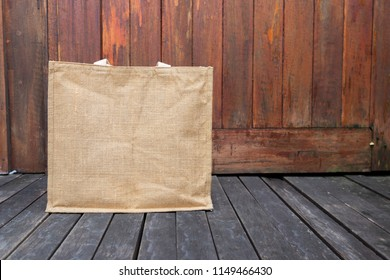 Jute bag on wooden floor with space on wood background, eco friendly bag, grocery shopping bag