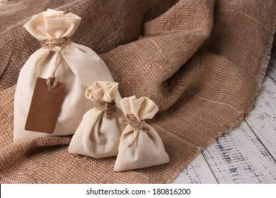 Jute bags on sackcloth, on wooden background
