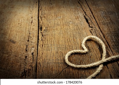 jute rope in heart shaped isolated on wooden background