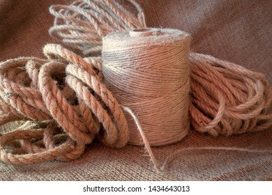 Jute rope and spools of burlap threads or jute twine on sackcloth fabric in close-up