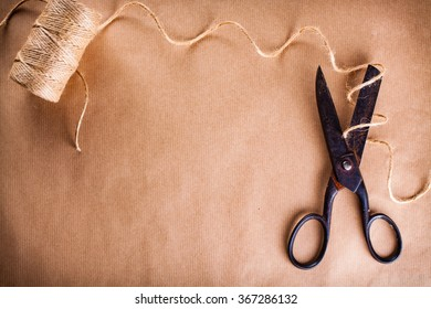 Jute twine and old scissors on wrapping paper background.