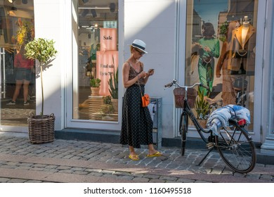 Jutlandia, Denmark - august 9, 2018: Woman consulting her mobile phone next to her bicycle with the windows of a trade in the background, in the urban center of the city of Aarhus