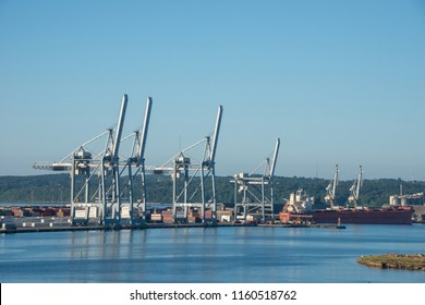 Jutlandia, Denmark - august 9, 2018: Cranes lined up at a loading dock and merchant ship at the docks of the industrial port of Aarhus