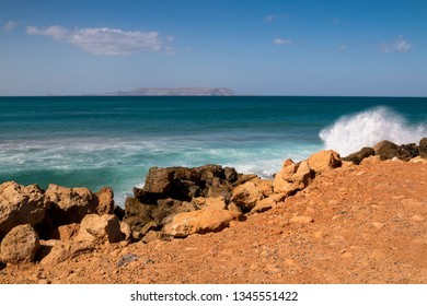 Jutty to the sea, built from an orange soil, lined by rocks, breaking the waves. Emerald color of the Mediterranean sea water, with its horizon, with a mountain. Gouves, Crete, Greece.