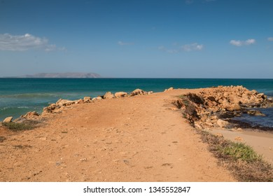 Jutty to the sea, built from an orange soil, lined by rocks. Emerald color of the Mediterranean sea water, with its horizon, with a mountain. Blue sky with little clouds. Gouves, Crete, Greece.