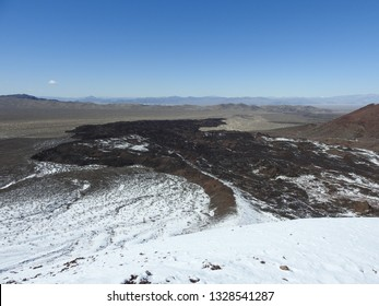 A juxtaposition of ancient lava and snow at the Cinder Cone Natural National Landmark within the Mojave National Preserve.