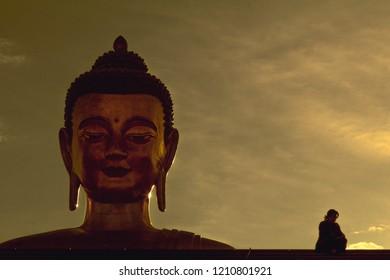 Juxtaposition; Budhha monument and girl; Girl sitting beside giant Budhha; Budhha headin sky