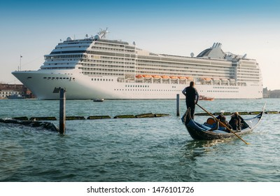 Juxtaposition of gondola and huge cruise ship in Giudecca Canal. Old and new transportation on the Venice Lagoon - Unidentifiable people and property