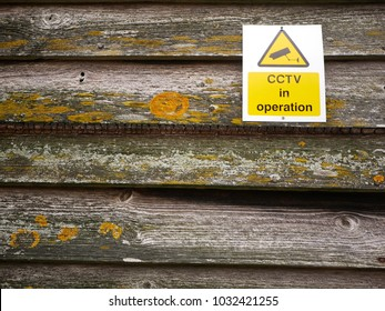 Juxtaposition of old wooden fence with lichen on side of barn on rural farm with modern sign warning that cctv is in operation