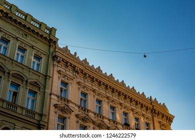 Juxtaposition. Pair of sneakers hanging high up above city street in the old center of Prague, the capital of Czech Republic, next to antique beautiful old residential buildings. Clear blue sky summer