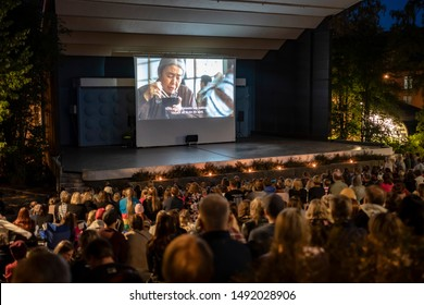 "Jyvaskyla, Finland - August 27, 2019: Cinema picnic in Lounaispuisto park. Free entrance event. People watching ""Shoplifters"" - 2018 Japanese drama film that won Palme d'Or at Cannes Film Festival."