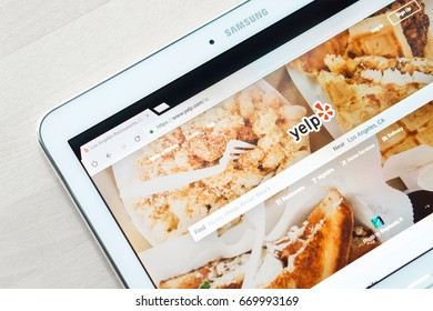 JYVASKYLA, FINLAND - JULY 1, 2017: Yelp home page on tablet screen. Yelp is a website that publish crowd-sourced customer reviews and ratings for local businesses. Editorial.