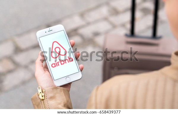 JYVASKYLA, FINLAND - JUNE 12, 2017: Woman showing Airbnb logo on mobile phone with baggage in the background. Airbnb is an online marketplace offering people a service to rent short-term lodging.