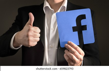 JYVASKYLA, FINLAND - JUNE 13, 2017: Business man giving thumbs up with a cardboard Facebook logo. Facebook is a popular social media platform launched in 2004. Illustrative editorial.