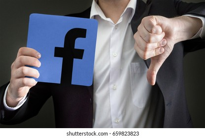 JYVASKYLA, FINLAND - JUNE 13, 2017: Man in a suit giving thumbs down with a cardboard Facebook logo. Facebook is a popular social media platform launched in 2004. Illustrative editorial.