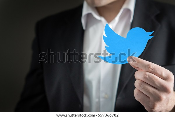 JYVASKYLA, FINLAND - JUNE 13, 2017: Man dressed like business person with a paperboard Twitter logo. Twitter is a social media network that was founded in 2006. Illustrative editorial.