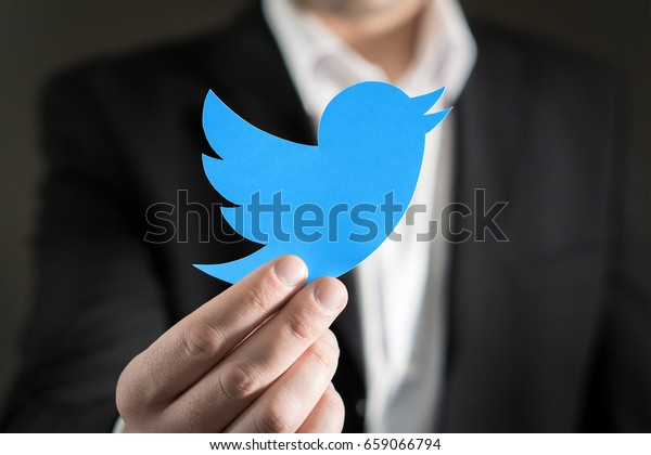 JYVASKYLA, FINLAND - JUNE 13, 2017: Close up of man in a suit showing printed Twitter logo. Twitter is a social media network that was founded in 2006. Illustrative editorial.