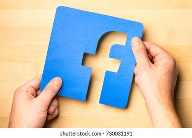 JYVASKYLA, FINLAND - OCTOBER 7, 2017: Hands holding Facebook logo cut from cardboard paper against wooden table. Facebook is a popular social media platform launched in 2004. Illustrative editorial.