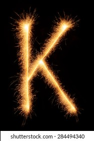 """""""K"""" letter drawn with bengali sparkles isolated on black background"""