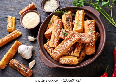 Kaasstengels, popular salty cheesy sticks or cheese puffs with cheese, sesame seeds on top, served in a clay dish, with sauce, top view, close up on a wooden table