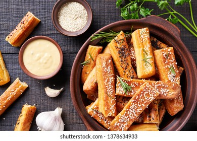Kaasstengels, popular salty cheesy sticks or cheese puffs with cheese, sesame seeds on top, served in a clay dish, with sauce, top view, close up on a wooden table, flat lay, horizontal