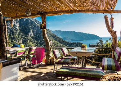 KABAK, TURKEY : restaurant with colorful chairs with a sea view and mountains