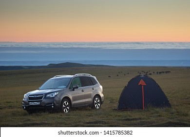 Kabardino-Balkaria region, Russia - August 2018: Subaru Forester car and a tent for outdoor recreation in the mountains on the background of the horizon line and clouds in the early morning