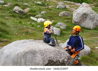 KABARDINO-BALKARIA, RUSSIA - JULY 31, 2018: father and son inspect the climbing equipment in the mountain camp of Bezengi (Caucasian region)