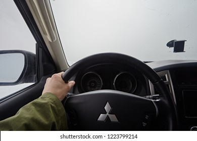 Kabardino-Balkaria, Russia - Oktober 2017:  Close-up of the hands of the driver on the steering wheel of a car mitsubishi pajero. A man traveling to the clouds, only a void is visible in the window.
