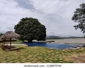 Kabini, Karnataka/India- July 20, 2018: The swimming pool and the the Kabini River beyond at the Evolve Back Resort