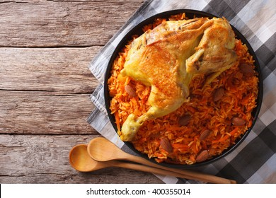 Kabsa of chicken with rice and vegetables on a plate. horizontal view from above