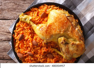 Kabsa - spicy rice with vegetables and chicken on a plate close-up. horizontal view from above