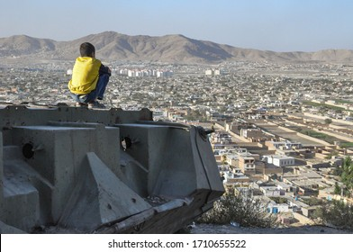 KABUL/ AFGHANISTAN 2012: Boy sitting on Destroyed Tank on the hills over Kabul City in Afghanistan