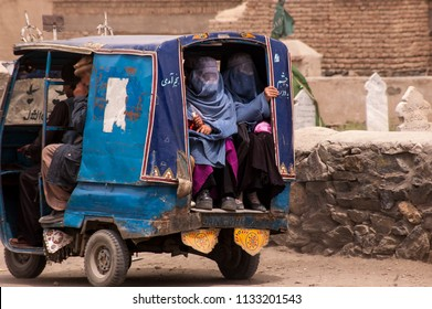 "Kabul, Afghanistan April 2004: Afghan women in burqas ride in the back of a taxi (""tro--tro"") near to Kabul"
