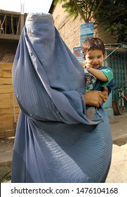Kabul / Afghanistan - Aug 16 2005: Woman dressed in a blue burqa (burka) holding a child in Kabul, Afghanistan. Kabul is the capital of Afghanistan. Mother, child, burqa, burka, Kabul, Afghanistan.