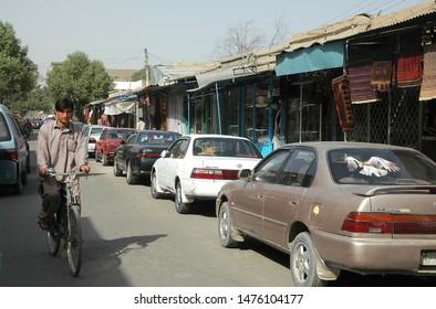 Kabul / Afghanistan - Aug 16 2005: A man cycles along a road in Kabul, Afghanistan. Kabul is the capital of Afghanistan. Road, cyclist, man cycling, bicycle, shops, stores, cars, Kabul, Afghanistan.