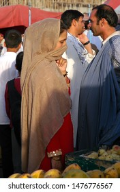 Kabul / Afghanistan - Aug 17 2005: A young woman in traditional dress at the market in Kabul, Afghanistan. The woman is wearing a headscarf. Girl, woman, head scarf, market, fruit, Kabul, Afghanistan.