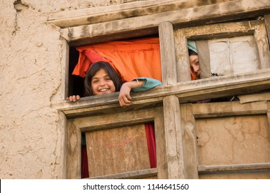 Kabul, AFGHANISTAN August 2004 : shy Afghan girls looking out a