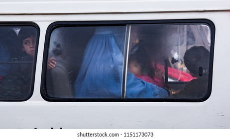 Kabul, Afghanistan, Feb 2005: Burqa-clad woman and children on a Kabul bus
