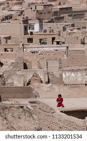 Kabul, Afghanistan, Mar 19 2004: Girl in a red dress against the colours of a Kabul neighbourhood
