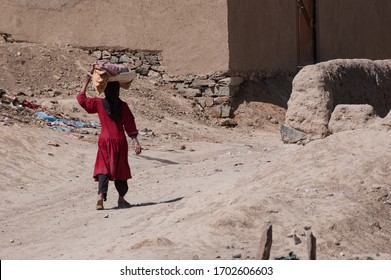 Kabul, Afghanistan - March 2004: Young girl walks home carrying bread