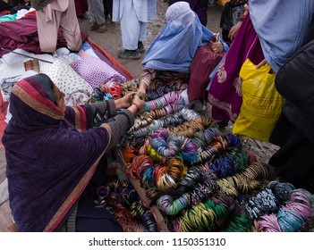 Kabul, Afghanistan, March 2005: Woman looking at bracelets in Kabul market stall