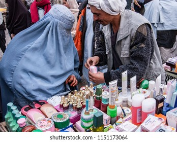 Kabul, Afghanistan, March 2005: Woman buys toiletries from Kabul market stall