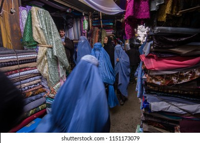 Kabul, Afghanistan, March 2005: Woman looking at cloth in Kabul market stall